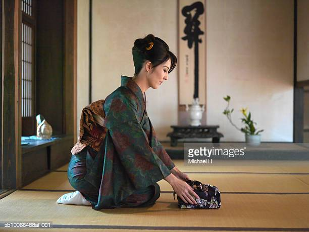 Japan, Kyoto, Enko Temple, woman in kimono presenting gift in temple