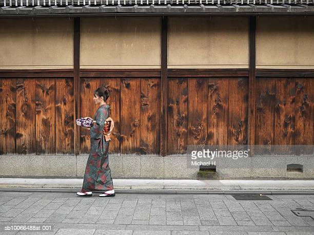 Japan, Kyoto, Gion, woman in kimono carrying wrapped gift in street