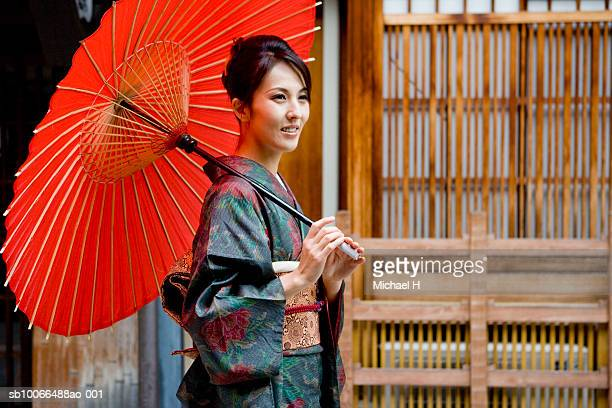 Japan, Kyoto, Gion, woman in kimono with red oilpaper umbrella, outdoors