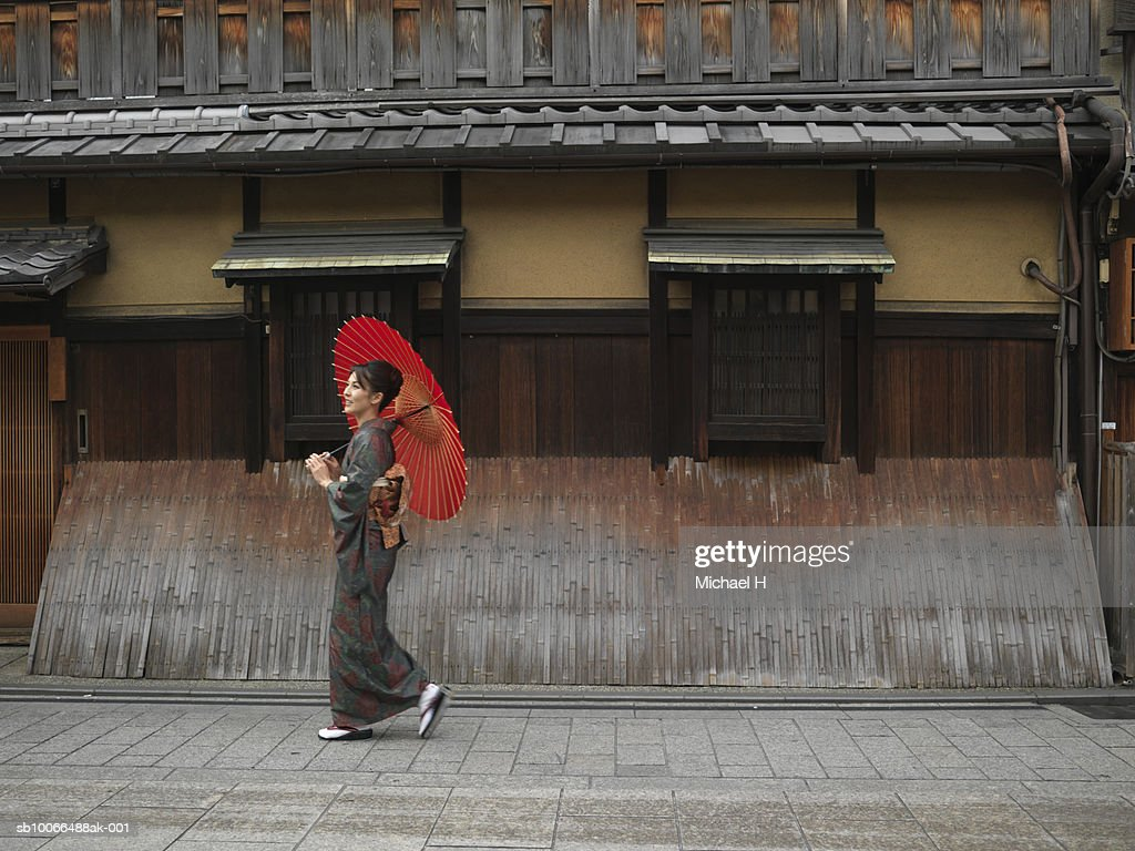 Japan, Kyoto, Gion, woman in kimono with red oilpaper umbrella, walking in street : Stock-Foto
