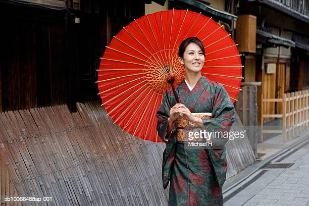 Japan, Kyoto, Gion, woman in kimono with red oilpaper umbrella, walking in street