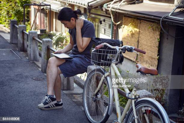 Japan, Kyoto Prefecture, Kyoto City,   young man with bicycle and tablet checking route