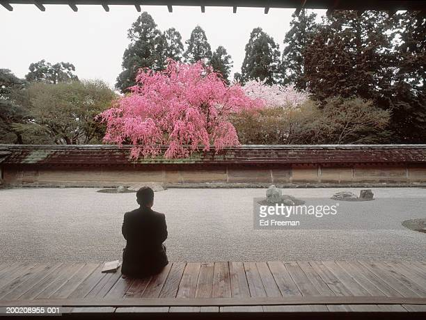 Japan, Kyoto, Ryoanji Temple, businessman sitting by Zen garden