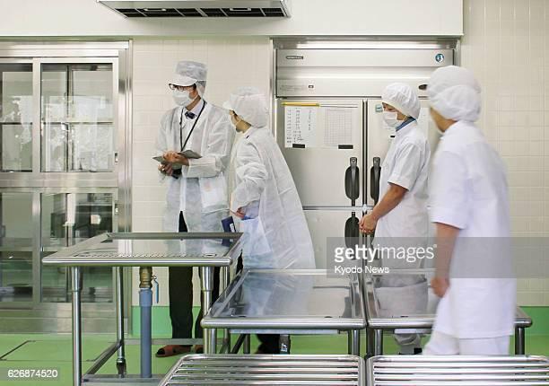 HAMAMATSU Japan Local health officials examine an elementary school kitchen in Hamamatsu Shizuoka Prefecture on Jan 17 after 905 students at 14...