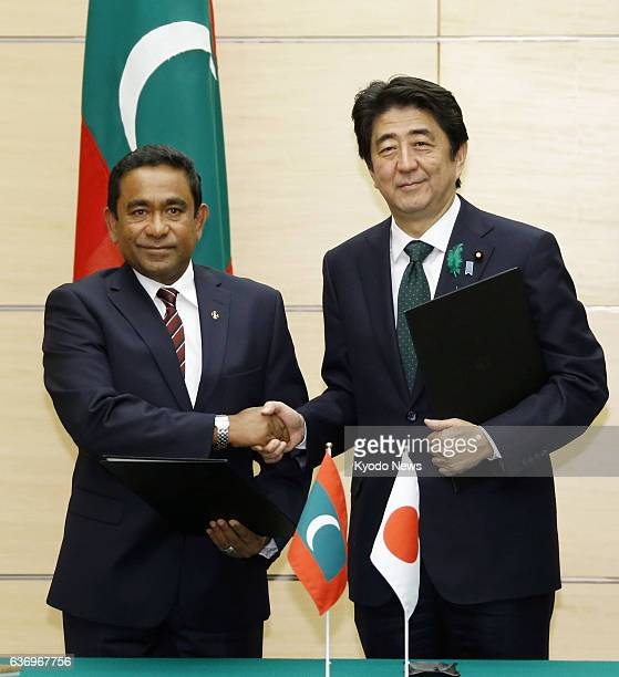 TOKYO Japan Maldives President Abdulla Yameen and Japanese Prime Minister Shinzo Abe shake hands after signing a joint statement in Tokyo on April 15...