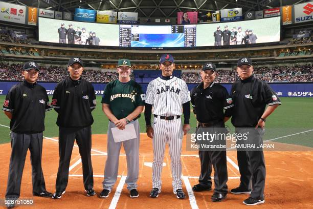 Japan Manager Atsunori Inaba and Australia Manager Steven Fish pose for photographs with umpires prior to the game one of the baseball international...