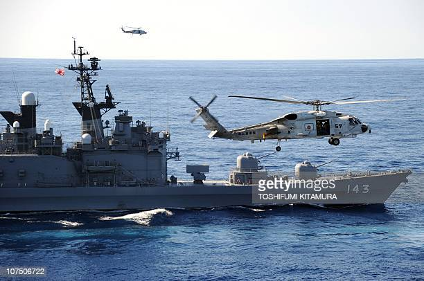 """Japan Maritime Self Defense Forces' helicopter flies beside Japanese destroyer """"Shirane"""" during the 'Keen Sword', a US-Japan military exercise at the..."""