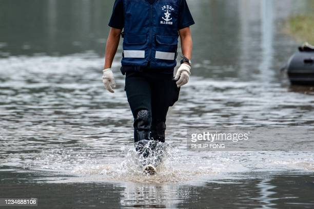 Japan Maritime Self-Defense Force member wades through a flooded area in Takeo City, Saga Prefecture on August 15, 2021.