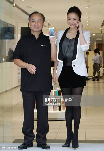 TOKYO Japan Masayoshi Son chairman and chief executive officer of mobile phone carrier Softbank Mobile Corp and actress Aya Ueto attend the iPhone 5...