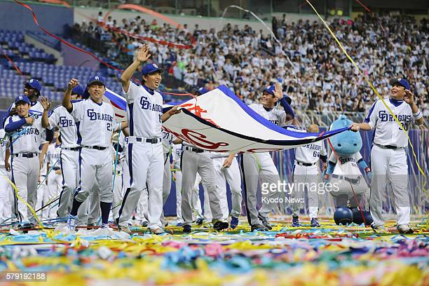 Japan - Members of the Chunichi Dragons carry a banner celebrating their Central League title in front of their supporters at their home stadium...