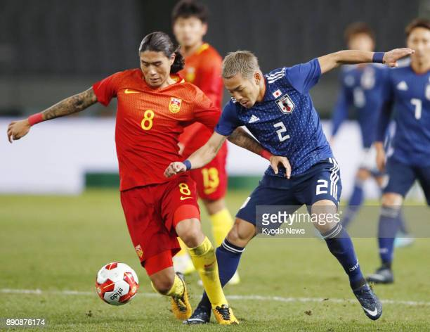 Japan midfielder Yosuke Ideguchi and China striker Xiao Zhi tussle for the ball in the first half of a men's match in the E1 Football Championship at...
