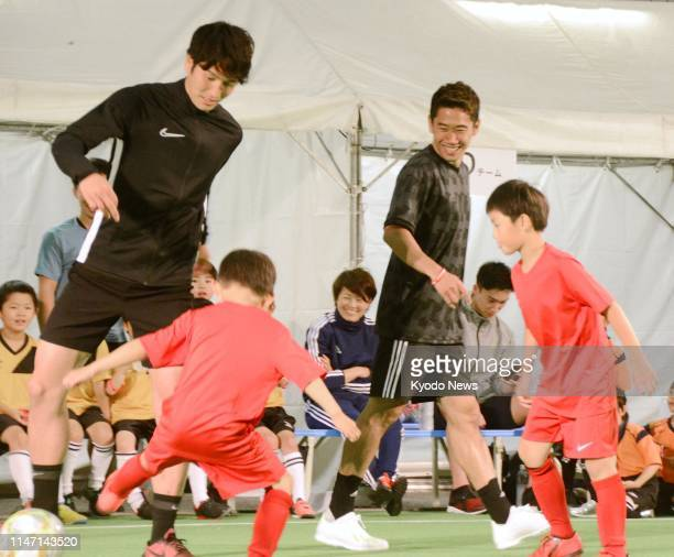Japan midfielders Shinji Kagawa and Genki Haraguchi who belong to Turkey's Besiktas and Germany's Hannover respectively play football with children...