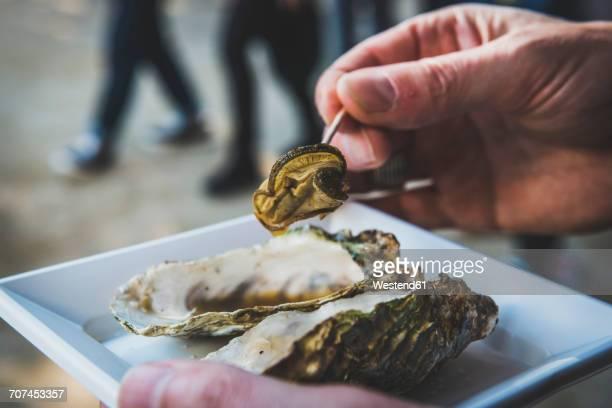 Japan, Miyajima, Man eating grilled oysters