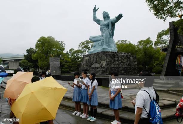 Japan / Nagasaki /Japanische Schüler vor der 10 Meter hohe Friedensstatue von Kitamura Seibo in der AtombombenGedenkstätte von Nagasaki aufgenommen...