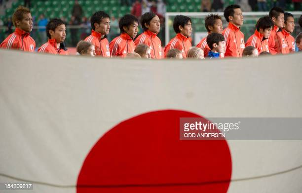 Japan national team's players listen to their national anthem behind their national flag on October 16 2012 at the municipal stadium in Wroclaw...