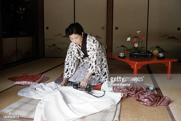 Japan. Novembre 1958- Reportage sur le mode de vie japonais: la famille ITOMI à Tokyo; Mme ITOMI ou Mme 'Règle de Beauté', repasse au fer electrique,...
