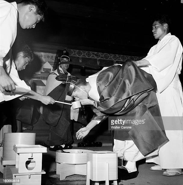 Japan. Novembre 1958- Reportage sur le mode de vie japonais: la famille ITOMI à Tokyo; un prêtre Shinto vêtu d'un hakama de couleur blanc et portant...
