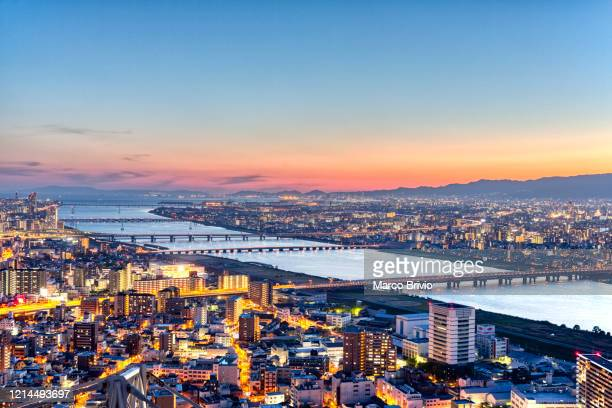 japan osaka. cityscape at sunset and yodo river - marco brivio stock pictures, royalty-free photos & images