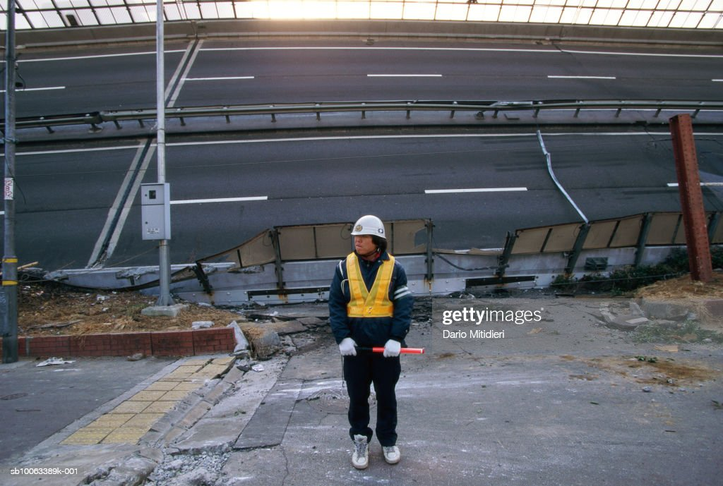 Japan, Osaka, Kobe, emergency services worker by road destroyed in earthquake
