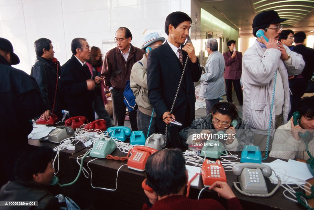 Japan, Osaka, people using phones in headquarters during earthquake