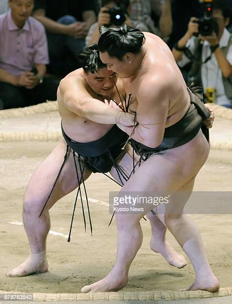 NAGOYA Japan Ozeki Harumafuji sends yokozuna Hakuho out of the dohyo at Aichi Prefectural Gymnasium in central Japan on July 23 capturing his second...