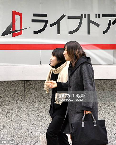 Pedestrians walk before a security brokage of the Livedoor Securities a subsidiary of Japan's successful Internet company Livedoor group in Tokyo 18...