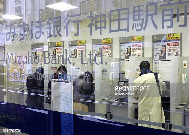 Japan - People use the automated teller machines at a Mizuho Bank branch in Tokyo on March 22, 2011. The large bank resumed ATM services after...
