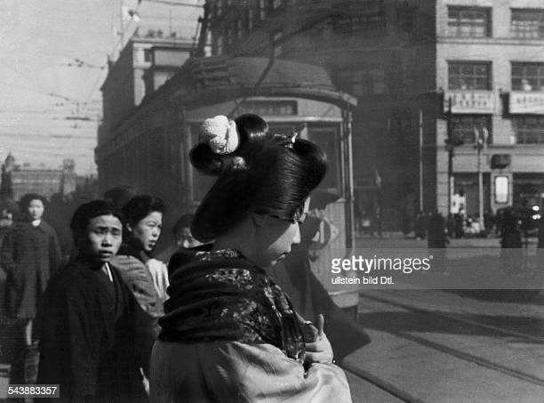 Japan Photo reportage about everyday life of a geisha a geisha in the evening on a busy street 1941 Photographer Weltrundschau Neudin Published by...