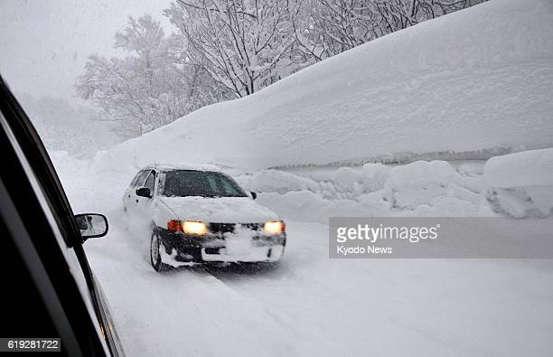 AOMORI Japan Photo shows a car driving on a road sandwiched by snow walls near Sukayu a hot spring resort area in Aomori Prefecture on Feb 25 2013...