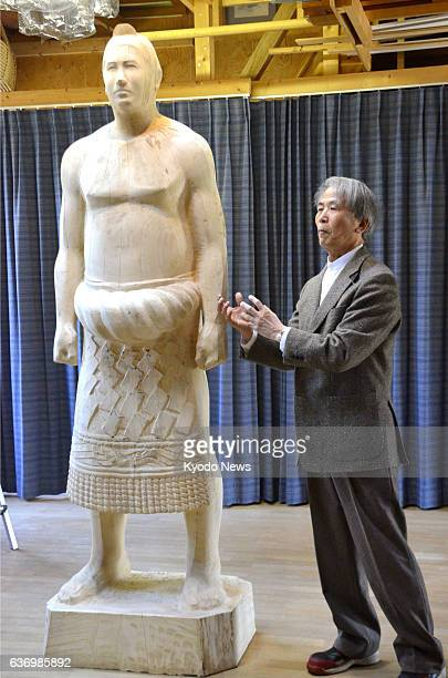 AKITA Japan Photo shows sculptor Toshio Kamada unveiling a wooden model he has carved for a statue of the late sumo great Taiho whose real name was...