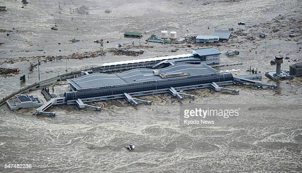 TOKYO Japan Photo taken from a Kyodo News helicopter shows Sendai airport in Miyagi Prefecture submerged by a massive tsunami triggered by a powerful...