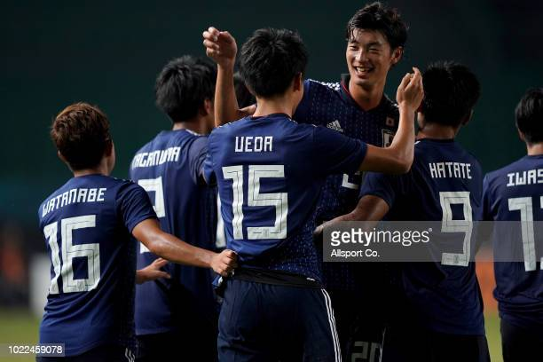 Japan players celebrate after Ueda Ayase scored from the penalty spot during the Men's Football round of 16 match between Malaysia and Japan at the...