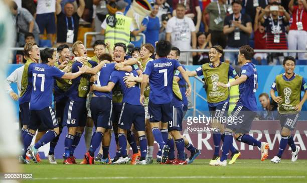 Japan players celebrate the team's second goal scored by Takashi Inui during the second half of a World Cup roundof16 match against Belgium in...