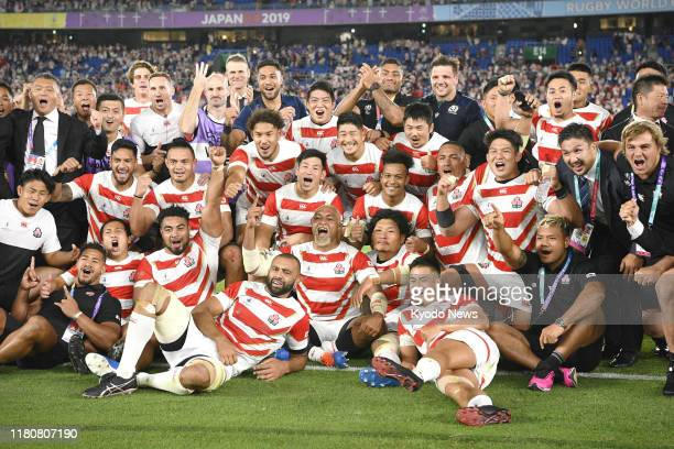 Japan players pose for a photo after defeating Scotland in a Rugby World Cup Pool A match in Yokohama near Tokyo on Oct 13 booking a place in their...
