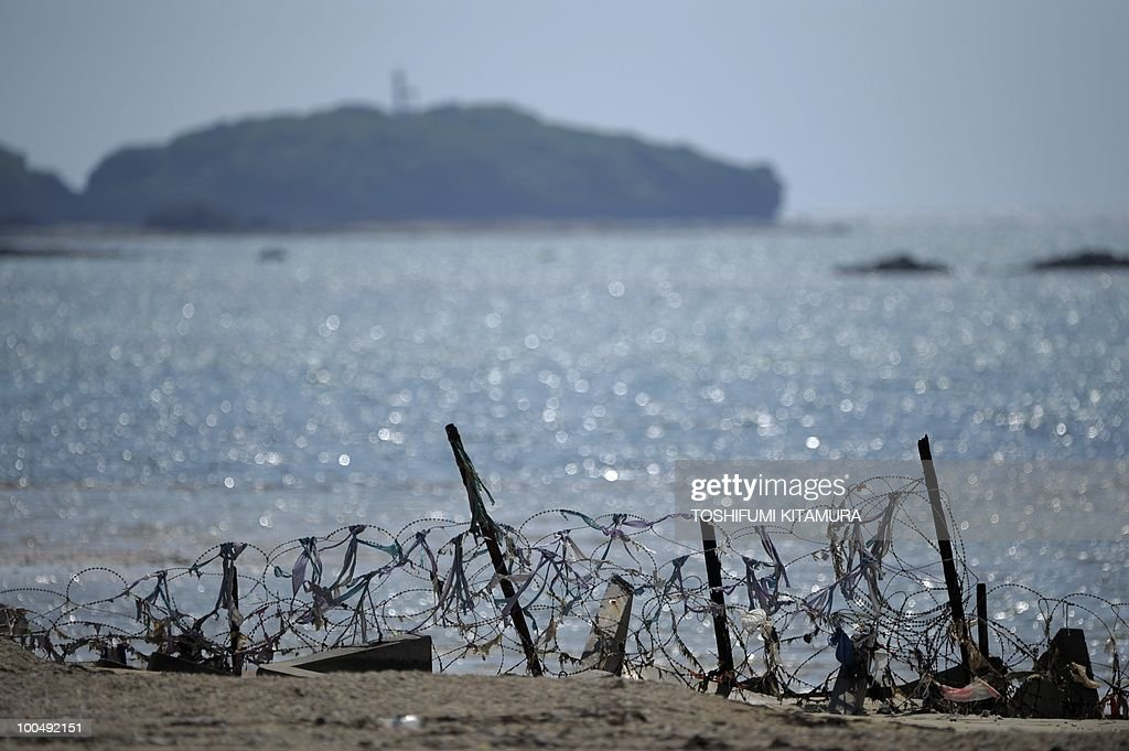 'Japan PM's coalition strained by US base deal'. (FILES) Barbed wire and a blockade divides the US Marine Corps facilities of Camp Schwab from the rest of the city of Nago in Okinawa prefecture on April 25, 2010. Japan's Premier Yukio Hatoyama faced a fresh political headache when a left-leaning coalition partner attacked his plan to allow for a US airbase to be relocated within Okinawa island.
