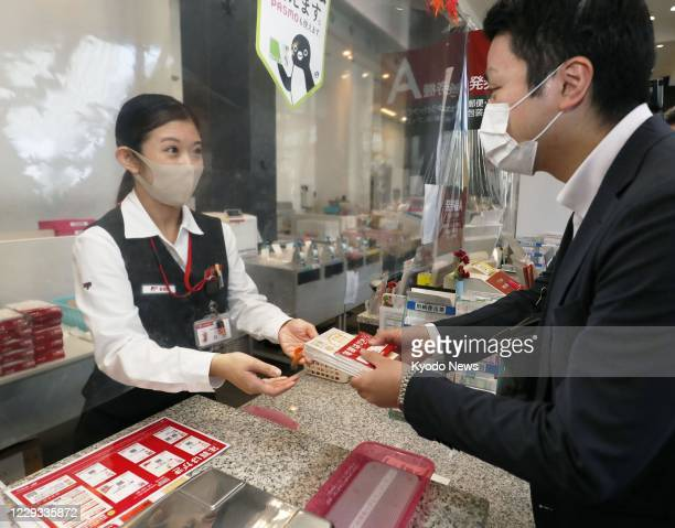Japan Post Co. Employee hands a bundle of 2021 New Year's cards to a man at a post office in Tokyo on Oct. 29 the first day of the nationwide sale of...