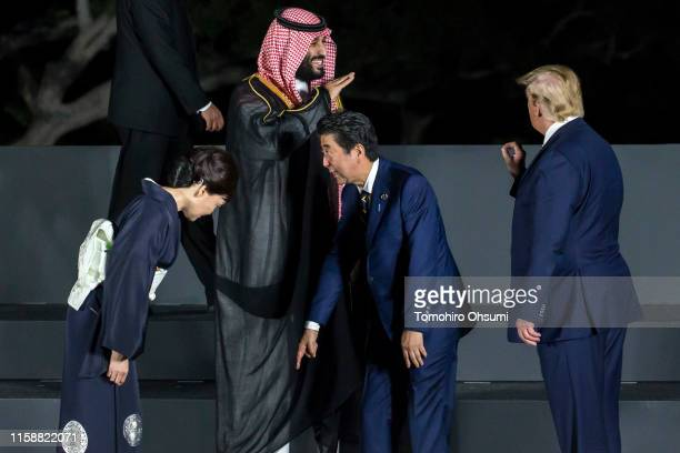 Japan' Prime Minister Shinzo Abe checks his position with his wife Akie Abe as Saudi Arabia's Crown Prince Mohammed bin Salman speaks to U.S....