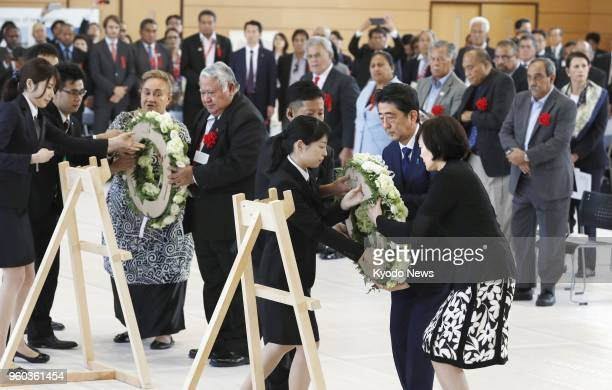 Japan Prime Minister Shinzo Abe his wife Akie and other national leaders present flowers to students during an event on May 18 at Iwakikaisei High...