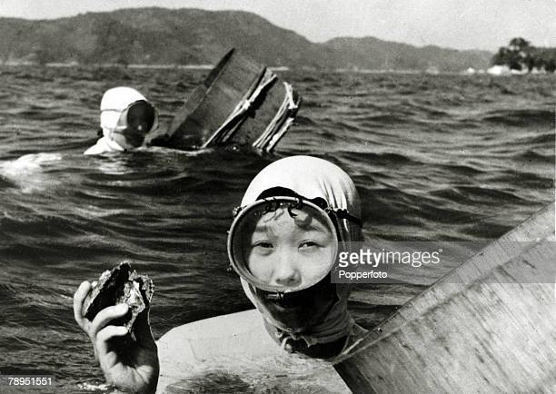 1959 Japanese girl divers who collect oysters from the sea and river estuaries pictured at work with the containers in which oysters which hold the...