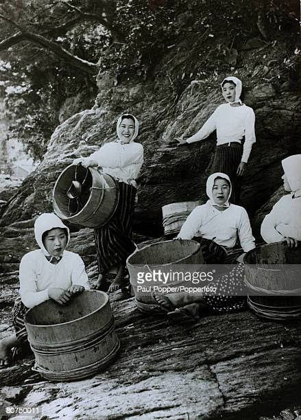circa 1950 Japanese girl divers who collect oysters from the sea and river estuaries with the tubs in which oysters which hold the cultured pearls...