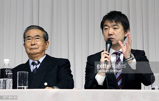 Japan Restoration Party acting president Toru Hashimoto speaks while their president Shintaro Ishihara listens during their campaign pledge...