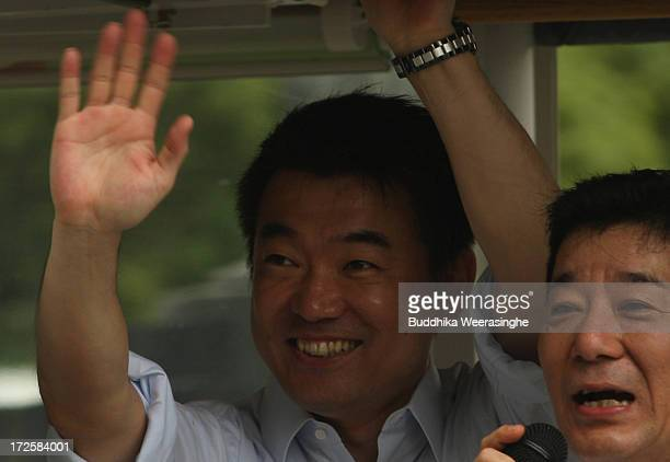 Japan Restoration Party deputy leader Osaka Mayor Toru Hashimoto waves to suppoters which was made from the campaign car during his official election...