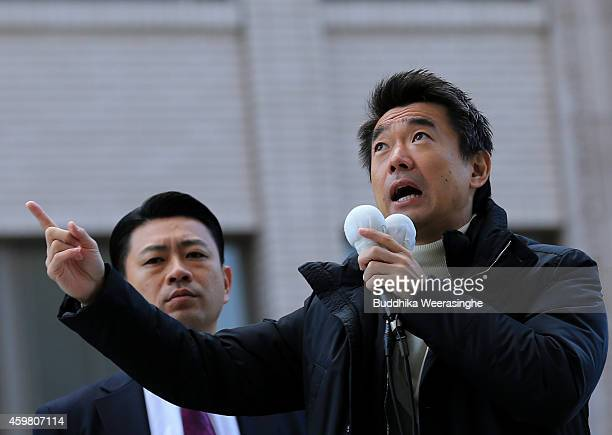 Japan Restoration Party leader Osaka Mayor Toru Hashimoto speaks to voters from the roof of the campaign car during his official election party...