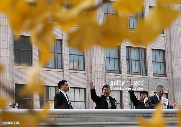 Japan Restoration Party leader Osaka Mayor Toru Hashimoto waves to suppoters as Osaka governor Ichirou Matsui and candidate Inoue Hidataka stand on...