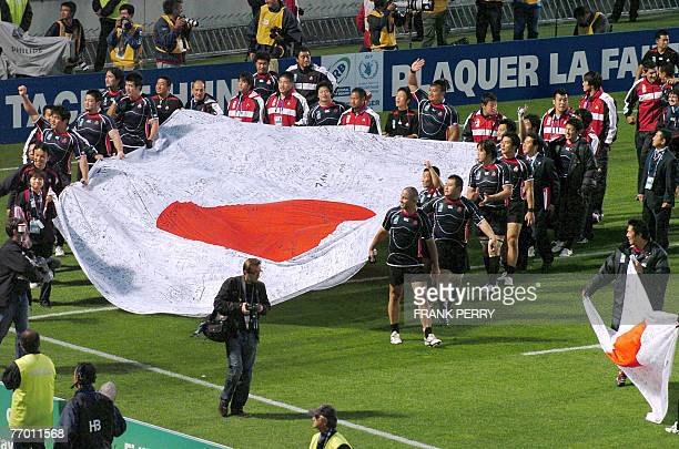 Japan rugby union players walk on the filed with their national flag at the end of the rugby union World Cup group B match Canada vs Japan 25...