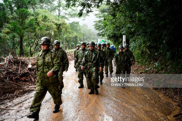 Japan Self-Defence Force soldiers walk in a devastated area caused by heavy rains in Ashikita, Kumamoto prefecture on July 7, 2020. - Emergency...