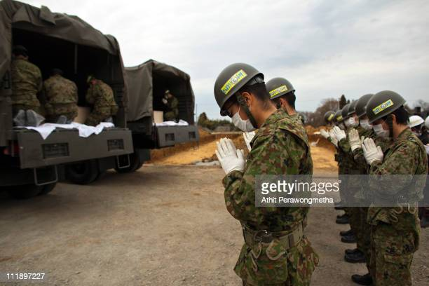 Japan SelfDefense Force members pay their respect to unidentified earthquake victims in vehicles during a mess funeral on April 8 2011 in Yamamoto...