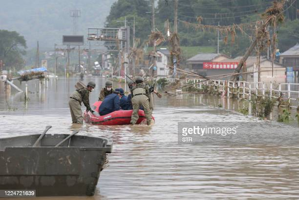 Japan Self-Defense Forces and police officers handle an inflatable boat to join rescue operations at a nursing home following heavy rain in Kuma...