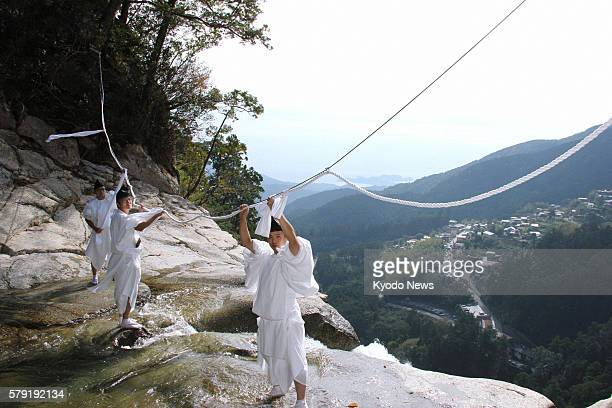SHINGU Japan Shinto priests set up a ''shimenawa'' sacred rope at the top of the Nachi Waterfall in the town of Nachikatsuura Wakayama Prefecture on...