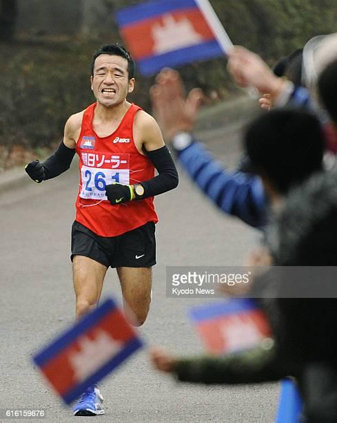 OITA Japan Spectators wave Cambodian flags on a road as comedianturnedrunner Hiroshi Neko runs in the BeppuOita Mainichi Marathon in Oita Prefecture...